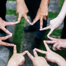 Women and men friends make star shape from fingers. Success, fri